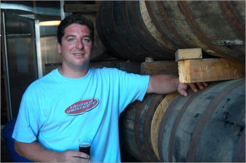 Jay Harmon of Cisco Brewers stands by racks of oak barrells full of aging bourbon whiskey. Private tours are available if you call ahead and make an appointment.