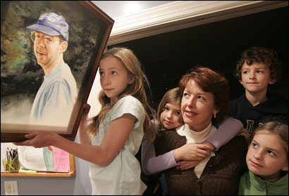 Lynn Osborn , mother of two sets of twins 8 and 11: Katie , 11 (holding picture of their dad Charley), Sarah, 8 (hugging mom from behind) Nicky , 8 (boy behind mother) and Ellen , 11 (far right) at their home in Belmont. Charley Osborn, the husband and dad, died four years ago from Lou Gherig's disease. Four years later her father, Lynn's, died in a car accident on a day she had shared breakfast with him.