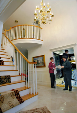 Carol Mader (left) and her designer Sandra Bissell, proprietor of Sandra Bissell Interiors, go over ideas for the stairs of Mader's home. Behind them on the ladder is Jenna Watkins, proprietor of Jenna Watkins Decoratives, who was painting in the study. (Globe Staff Photo/Jim Davis)