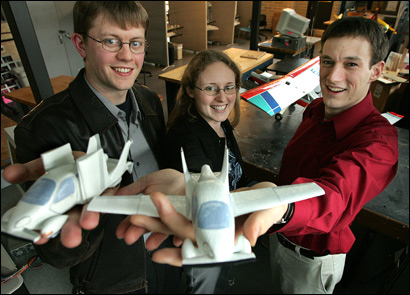 Carl Dietrich (left), Anna Mracek, and Samuel Schweighart, all licensed pilots, show off their flying car models at the Daniel Guggenheim Aeronautical Laboratory in Cambridge.