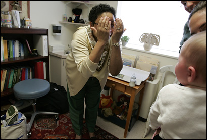 Dr. Johnye Ballenger, who is beloved by her patients, cheers up a crying baby in her office at Children's Hospital Boston.