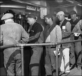In the lunch lines, workers would have their meals bought and paid for in 90 seconds. More than 50 thousand workers helped build warships and install huge gun turrets on the ships at the site. This undated photo shows men standing in line for their lunches.