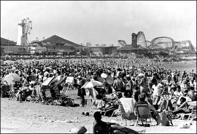 Revere Beach is crowded with sun worshippers and amusement park enthusiasts in 1962.