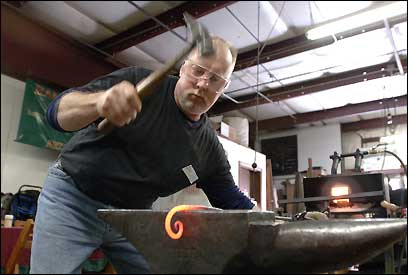 Jay Pinard hammers a piece of iron