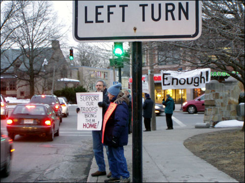 David Ascher (left) said the growing anti-war sentiment is out in the streets. He held an anti-war sign during Newton Dialogues on Peace and War's weekly vigil, and waved at cars that 'Honk for Peace.' He said about 120 people joined them in Newton Centre in January, and that drivers' responses were increasingly positive.