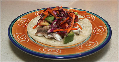 Fish taco with avocado salsa and carrot slaw