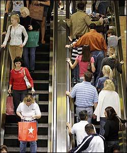Holiday shoppers crowd the mall escalators.