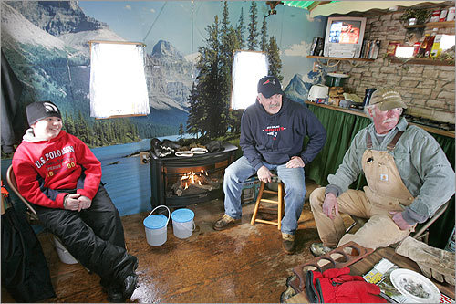 From left to right: Zack O'Brien of Nashua, Peter Muse of Meredith, and Bob Myshrall peer out the windows of Muse's bob house on Lake Winnipesaukee.