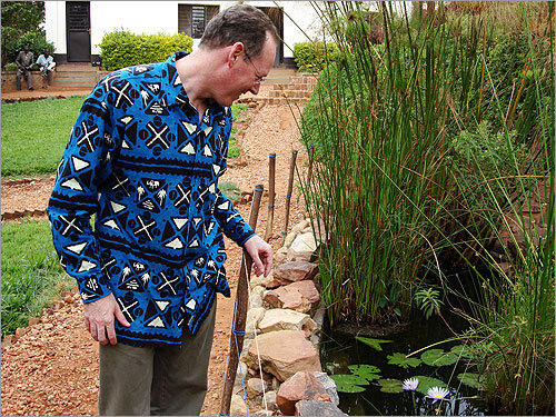 Farmer looks over his trademark fishpond at Rwinkwavu Hospital in eastern Rwanda. He and his brother Jeff built the pond and went into swamps to get the fish and flora.