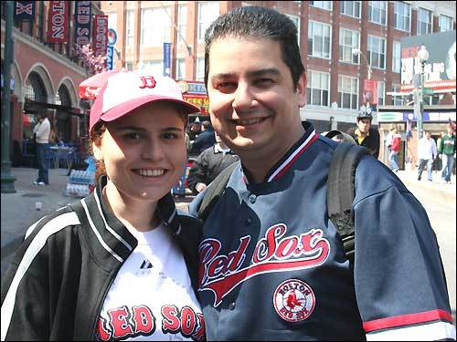 Chrissy and Costa Nikolaidis from Dedham visit their brother-in-law Harry Pateras at Fenway's Sausage Connection while they wait for the lead marathon runners to reach Kenmore.