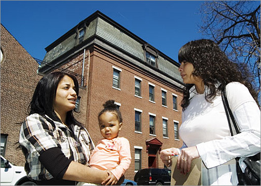 Case manager Crystal Belchior, right, talks with Raquel Gonzales, a resident at the Crossroads Family Shelter in East Boston, about her baby Jasmiah.