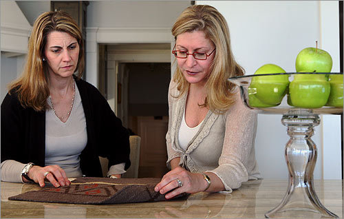 Designer Heather Wells (left) and Barbara Goldman go over a rug sample in Goldman's home. Her floors are made of a domestic walnut harvested from old trees that were about to die.