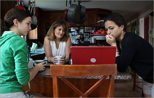 Anna Wilson (left) and her sister Meghan check out a social networking website as their mother, Deirdre Wilson, enjoys her morning coffee at home in Beverly.