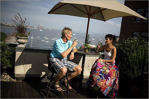 "Bernie Ortwein (left) and Karen Semmelman enjoy a glass of wine on their roof deck in the North End. The pair is in just their second season on their roof deck but already they can't imagine living without it. In 2006, the couple moved to the North End from the Chesapeake Bay area, where they'd gardened on 3 1/2 acres of waterfront property. ""I knew a lot about traditional gardening in the ground,"" Semmelman says. ""We knew nothing about gardening in containers."""