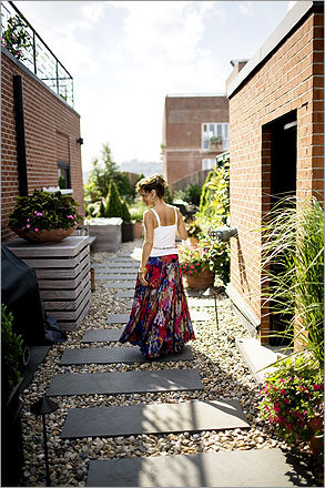 """Semmelman walks on her roof deck in the North End in Boston. With so many outdoor spaces, they often find it a challenge to figure out where to settle themselves. """"It's hard to leave,"""" Semmelman says. """"We used to go out to eat, but now we don't want to miss the time we have here."""""""
