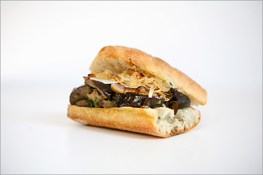Roasted egglant sandwich with meaty eggplant, parmesan, onions, and olives piled onto sliced crusty bread.
