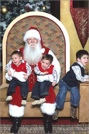 While Joshua and Zachary, 1, give in to Santa, Simon, 3, plans his escape. 'All three tried to make a run for it -- Simon took off one second later,' writes mom, Dana.