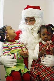 Santa, a.k.a. Beau Stubblefield-Tave, holds Ananda Scott (left) and Amara Hurd during a holiday party at the West Medford Community Center.