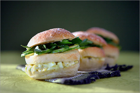 Layer creamy egg salad with cukes and parsley on small buns.