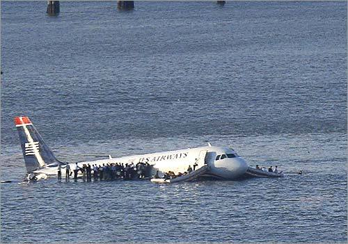The plane was submerged in the icy waters up to the windows, and rescue crews opened the door and pulled passengers in yellow life vests from the plane. Several boats surrounded the plane, which appeared to be slowly sinking.