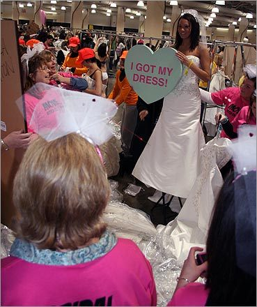 This magic moment? A group breaks into applause as this bride-to-be poses after finding her dress. The Running of the Brides, which takes place twice a year in Boston, kicked off at the Hynes Convention Center on February 20. Runners began lining up before 3 a.m., hoping to snag the perfect discount dress from Filene's Basement.