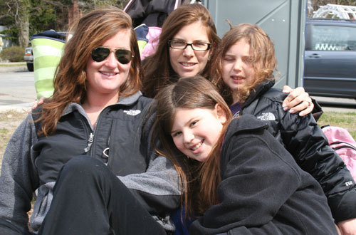 Dena Rashes of Newton, with her daughters Lily, 7, and Emma, 9, and their babysitter Erica Twomey of Brighton. Dena's watched the marathon for the past 15 years, and Lily says this is their reserved spot.