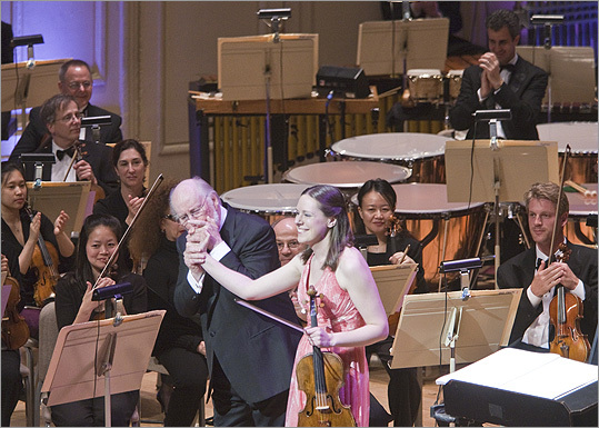 John Williams congratulates violist Cathy Basrak following her performance of the world premiere of Williams' Concerto for viola and orchestra with the Boston Pops. At the timpani, Basrak's husband Tim Genis applauds for his wife.