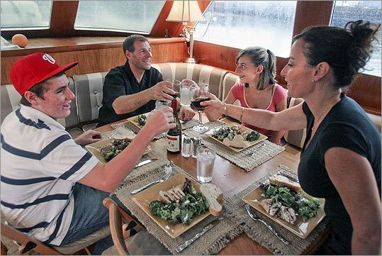 The Jost family sits down for dinner on their boat in Boston Harbor where they live.