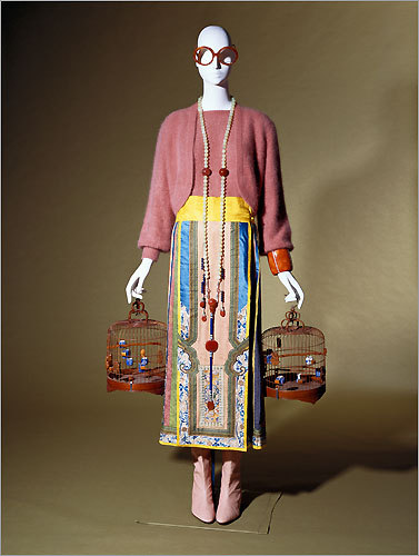 An ensemble from the fashion collection of Iris Apfel. Twin sweater set, Krizia, 1980s, Milan, Italy, angora wool knit. Skirt, Qing Dynasty (1644–1912), China, silk damask, brocade, satin with silk and filé thread embroidery. Mandarin necklace, Qing Dynasty (1644–1912), China, silk cord, carnelian, jade, metal. Cuff bracelet, about 1989, Europe; amber resin, rhinestones. Boots, designed by Iris Barrel Apfel and made by Canfora, about 1980, Capri, Italy, leather. Bird Cages, 1950s, China, bamboo, porcelain, metal.