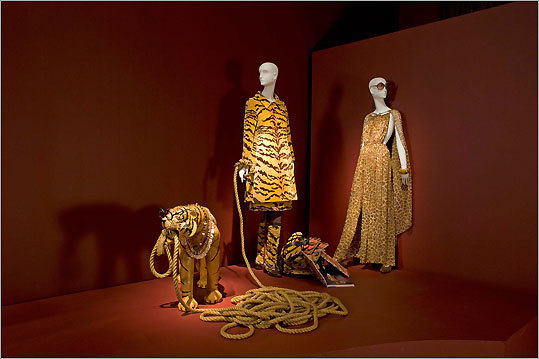 Ensembles from the fashion collection of Iris Apfel. Tiger travel ensemble. Iris Barrel Apfel by Contessa Adriana Biglia, circa 1965. Hand-woven silk velvet on linen warp upholstery fabric. Dress, James Galanos, circa 1970. Brown and beige giraffe-printed silk chiffon. Cuff bracelet, American, circa 1981. Wood, fabric, and rhinestones. Boots, Italian, circa 1990. Brown suede with leopard-printed gold lamé.