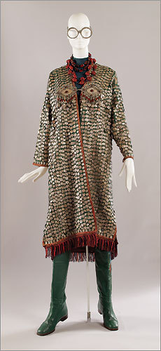 An ensemble from the fashion collection of Iris Apfel. Coat, Afghan, 20th century. Green linen/wool blend with applied silver metal coins and charms inset with turquoise and carnelian, and red and black wool fringe trim. Necklaces, Italian, mid-20th century. Faux coral beads with bone and brass. Boots, Italian, circa 1987. Green leather and multicolored cotton thread embroidery.
