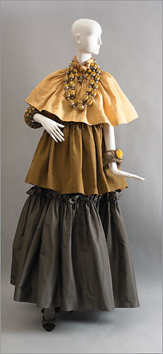 An ensemble from the fashion collection of Iris Apfel. Evening dress, Lanvin haute couture by Jules-Francois Crahay, circa 1985. Gold, brown, and pewter silk faille. Necklaces, Tibetan, early 20th century. Silver, amber, coral, and turquoise. Cuff bracelet, Bhutanese, late 19th century. Silver and amber. Cuff bracelet, Tibetan, late 19th century. Silver, amber, coral, and turquoise.