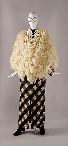 An eclectic ensemble from Iris Apfel's fashion collection. Cape, Nepalese, 1970s, ivory wool knit with fringe and self-fabric pompons. Skirt, Gianfranco Ferré, 1990s, black and beige buffalo-check wool. Necklace, Indian, early 20th century, silver and snail shells. Necklace, Monies, circa 1999, bone chips. Necklace, Chinese, circa 2003, carved bone. Necklace, Tibetan, circa 1970, carved bone. Bangles, Indian, early 20th century, ivory and wood. Boots, American, circa 1994, black synthetic suede cloth.