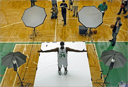 By Jim Davis, Waltham, September 28 This was shot at the Celtics annual media day, which is every year before the training camp. You have access to the players for a couple of hours where they pose for photos, do promotional spots for radio and TV, do interviews. There's a set of stairs that leads down to the court; you get a good overview of the court from up above. It's got good lines to it. It's graphically appealing with the four strobes in the corners. It wouldn't have been as good of a picture without Paul Pierce's arms stretched out like that. It kind of draws you into it.