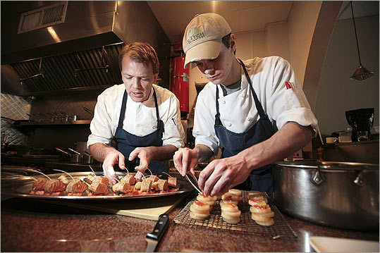 Christopher Parsons and Nathaniel French practice preparing lacquered salmon belly and rolls of salmon loin with fried foie gras (center photos) and a platter of salmon with pan-fried polenta topped with sauteed chard and mostarda.