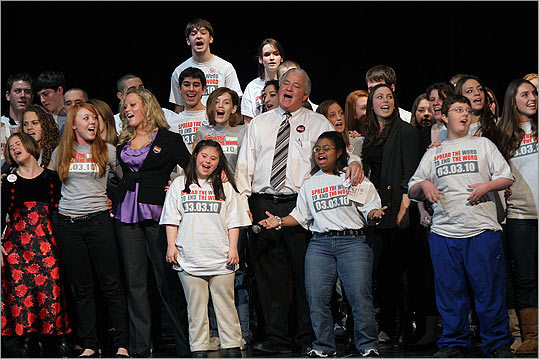 Winthrop High School teacher Chris Donnelly (above center) last week led students in song at a 'Spread the Word to End the Word' rally to discourage use of the word retarded.