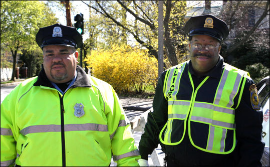 Auxiliary patrolmen Chris Desa and Jonathan McAfee guide traffic away from Commonwealth Avenue near Newton City Hall.