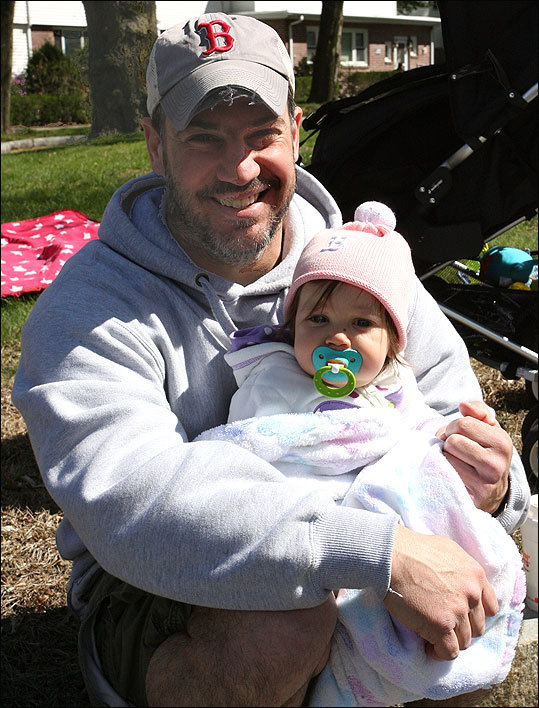 Ed Lavache, 39, from Watertown, continues a decades-long spectator tradition with his eight-month-old daughter Grace.