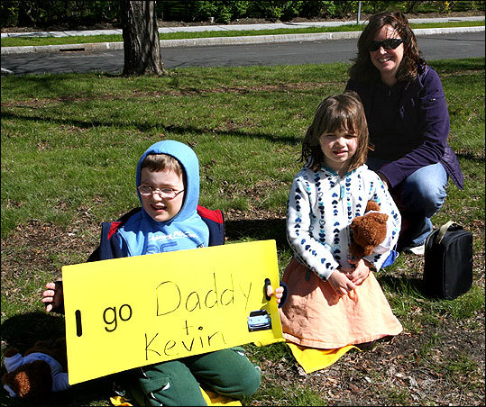 Jack, seven, and Sarah O'Reilly, five, with their mom Katie, 43, cheer for dad Ted in his first official Boston Marathon. Ted's running to raise money for the public school system of Higham, where the family's from.