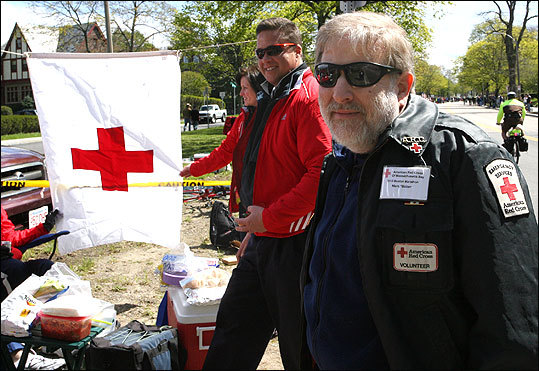 Volunteers Phil Scholten of Beverly and Marc Bober of Chelmsford at Red Cross Station 15, awaiting the arrival of the first women runners. Marc's been volunteering for 27 marathons; this is Phil's second race.