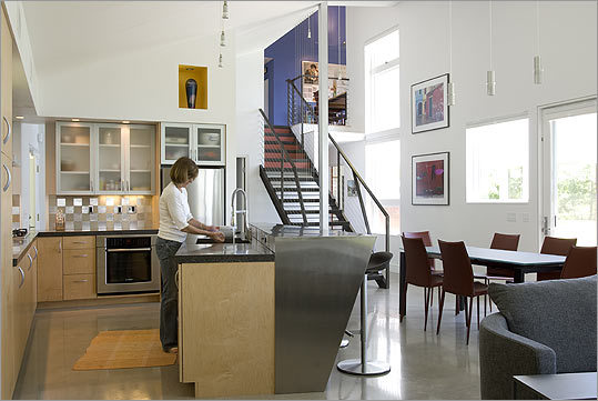ECHOES OF SOHO Polished concrete floors, high ceilings, and a steel-framed staircase give the home a loft-like feel.