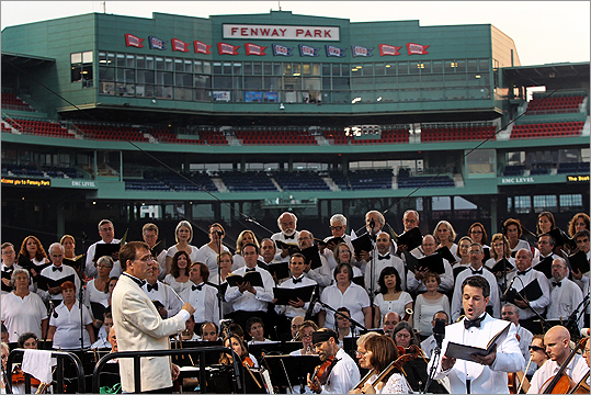 Boston Landmarks Orchestra conducting associate Christopher Wilkins, at left, with Matthew DiBattista, tenor, at right, against the backdrop of Fenway Park.