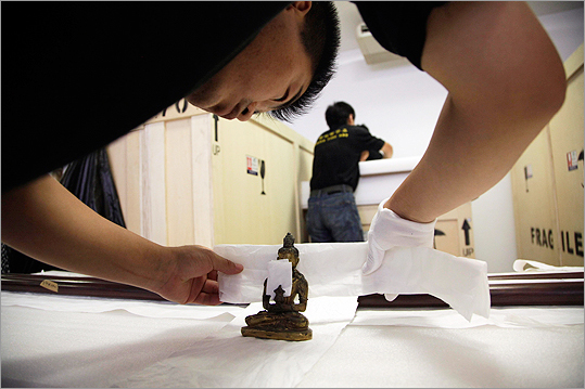A Chinese worker prepared a Buddha statuette for shipping at the Forbidden City in Beijing on July 28, 2010.
