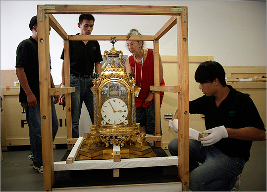 Peabody Essex Museum curator Nancy Berliner (in red) observes as workers pack an antique clock at the Forbidden City in Beijing. Berliner and four other museum staffers have been meticulously packing up the objects in the palace compound created by Emperor Qianlong in the 18th century and last occupied by Emperor Puyi.
