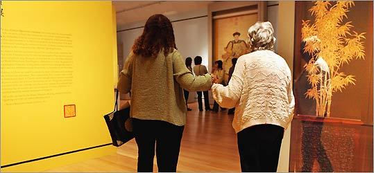 (left), leads Jean Sottile through a gallery at the Peabody Essex Museum in Salem.