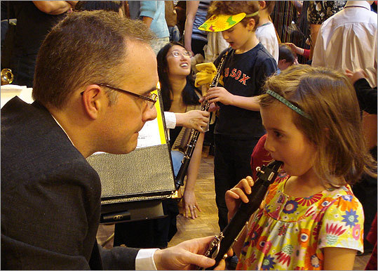 Clarinetist Ian Whiting (left) with a visitor at New Philharmonia's instrument petting zoo. (Rachel Hands)