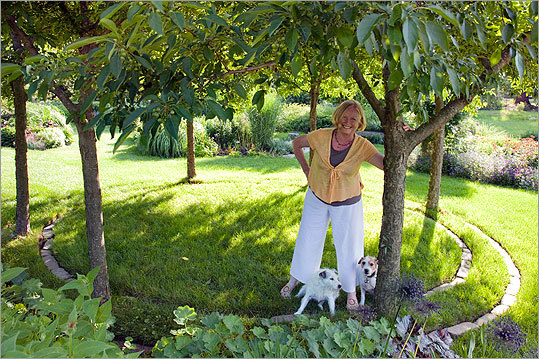 Homeowner Shirley Williams stands in the Sugar Tyme crabapple circle with two pals.