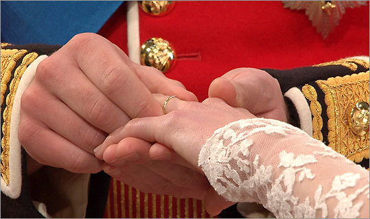 A closeup of Prince William putting a wedding ring on Kate Middleton's finger.