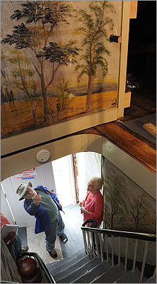 Homeowner Glenn Haines of East Baldwin, Maine points out the extensive 19th century folk art murals being removed from his home to Nelle Ely (right), president of the Rufus Porter museum where the work will be displayed. To remove these pictures means not only irking some preservationists but also literally tearing apart a 165-year-old house -- or risk that whoever owns it next might endanger the murals, purposefully or not.