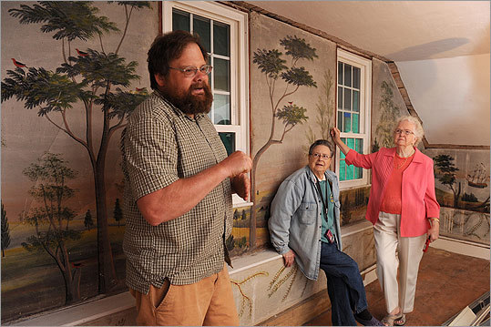 Arlington-based contractor and preservationist David Ottinger (left) discusses the project to remove folk art from the Haines home in East Baldwin, Maine, with owner Norma Haines, (center) and Nelle Ely. How does one remove an 18-foot section of antique plaster wall without it buckling, or crumbling to dust? Very carefully. 'Fortunately, because the house is not being demolished, we have more time to glue,' said Ottinger.